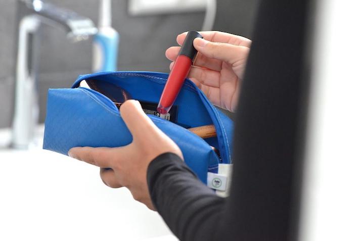 Lippenstift wird aus blauer Tasche genommen