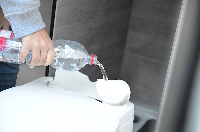 Spuelwasser mit Wasserflasche aufgefuellt